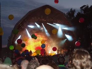 Brightly coloured balloons floating in front of a brightly lit stage