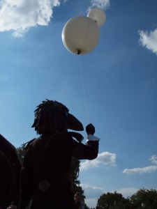 Man wearing a crow's head over his head holding two large white balloons